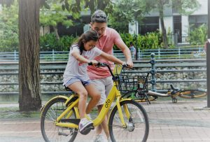 Father teaches a daughter to ride a bike.